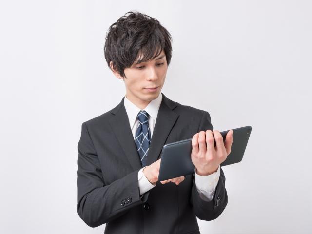 タブレットで計算するビジネスマン