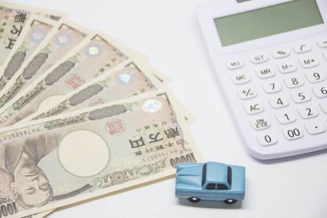 電卓とお金と車のおもちゃ