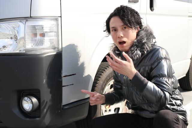 車の傷に驚く男性