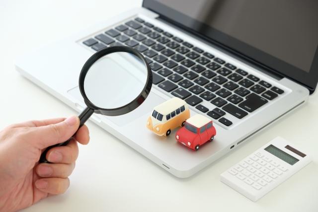 パソコンに置かれた車のおもちゃと虫眼鏡