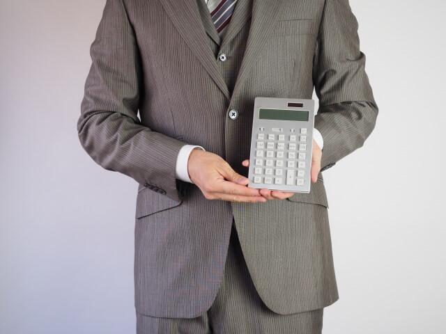 電卓を持ったビジネスマン